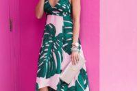 26 a pink midi dress with a tropical print, an asymmetrical skirt, a V-neckline, spaghetti straps, wedges and a metallic clutch