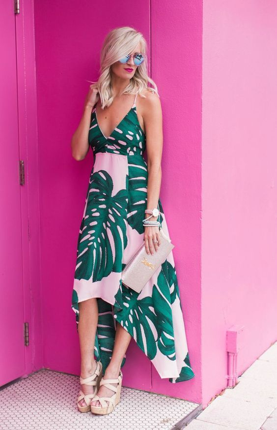 a pink midi dress with a tropical print, an asymmetrical skirt, a V-neckline, spaghetti straps, wedges and a metallic clutch