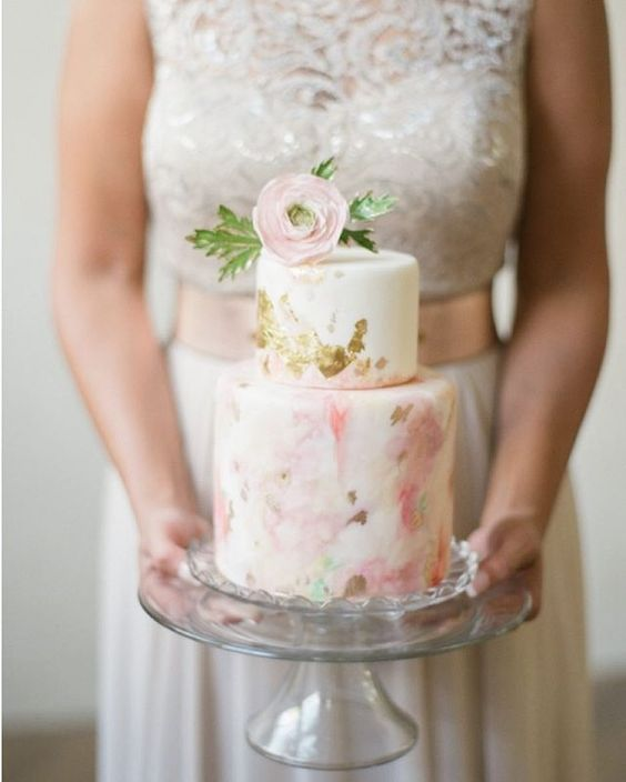 a tender handpainted watercolor wedding cake with gold leaf and a sugar flower on top for a spring wedding