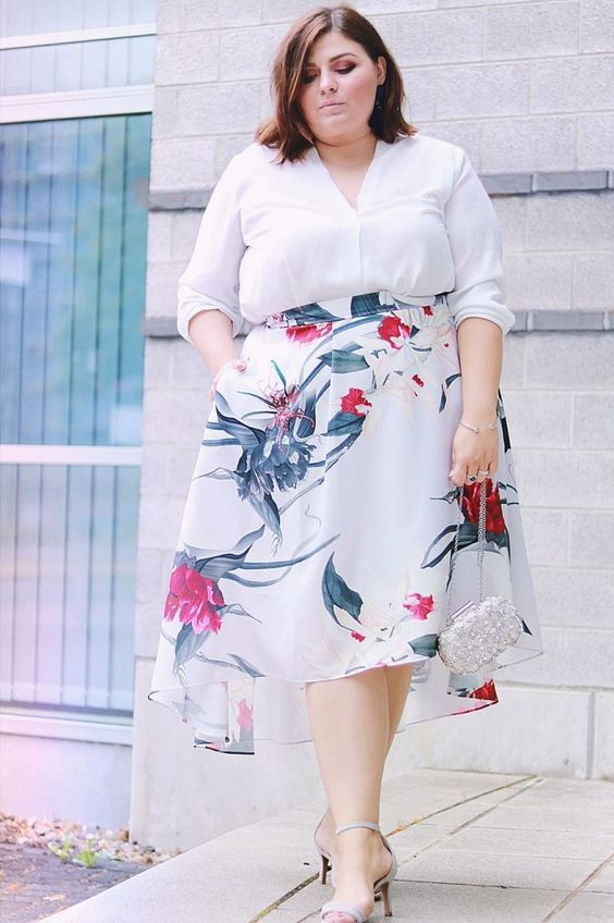 a white V-neckline shirt, a floral A-line asymmetrical skirt, metallic shoes and a clutch for a casual wedding