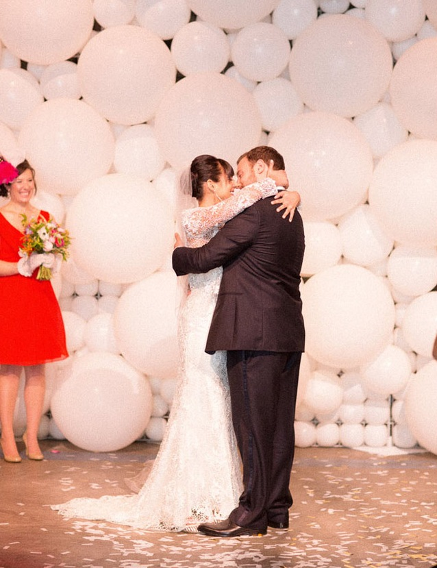 a white balloon wedding backdrop and lights hanging down make up a modern ceremony space