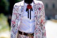 26 a white with pink floral print suit, a white shirt, a labeled belt, a pompom bolo tie