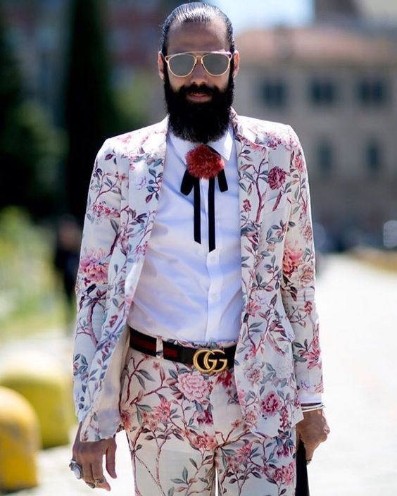 a white with pink floral print suit, a white shirt, a labeled belt, a pompom bolo tie