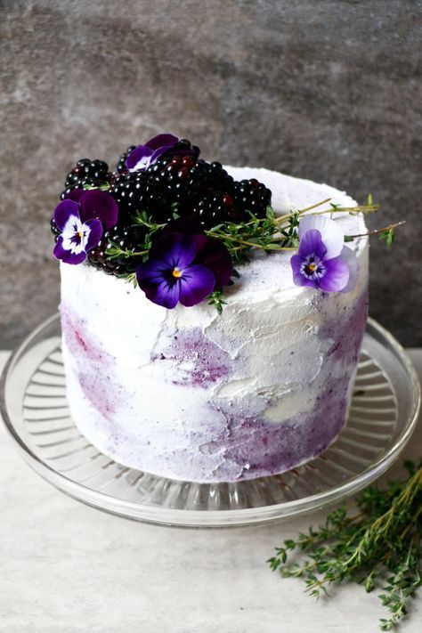a wholesome gluten-free and vegan wedding cake with blueberries and blackberries and some fresh blooms on top