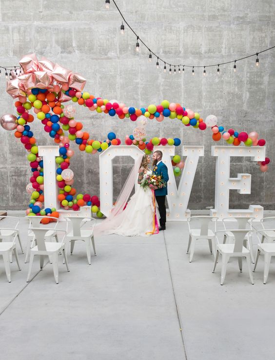 marquee LOVE letters decorated with super colorful balloons here and there is a veyr whimsy idea