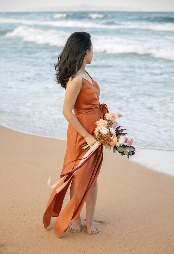 a refined rust wrap maxi dress with side slits, spaghetti straps and a sash for a beahc wedding