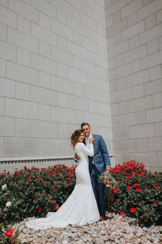a lace sheath wedding dress with long sleeves and a semi-cathedral train