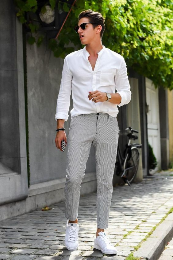 a relaxed outfit with a white shirt, grey thin stripe pants, white sneakers and sunglasses