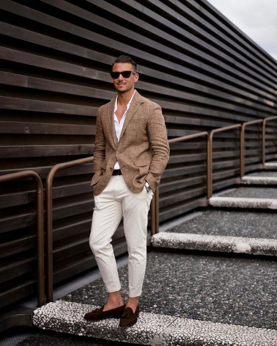 creamy cropped pants, a white shirt, a tan blazer and brown moccasins plus sunglasses for a beach wedding