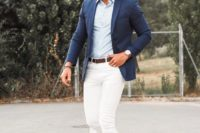 creamy jeans, a light blue shirt, a navy blazer, brown moccasins and sunglasses for a timeless beach look