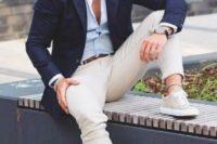 tan pants, a light blue shirt, a navy blazer, grey sneakers and stylish sunglasses