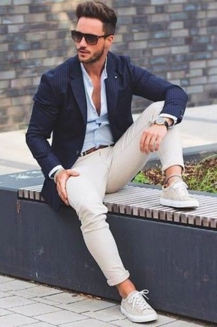 tan pants, a light blue shirt, a navy blazer, grey sneakers and stylish sunglasses