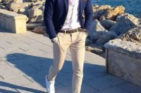 tan pants, a white shirt, a navy blazer and white sneakers that create a more modern look