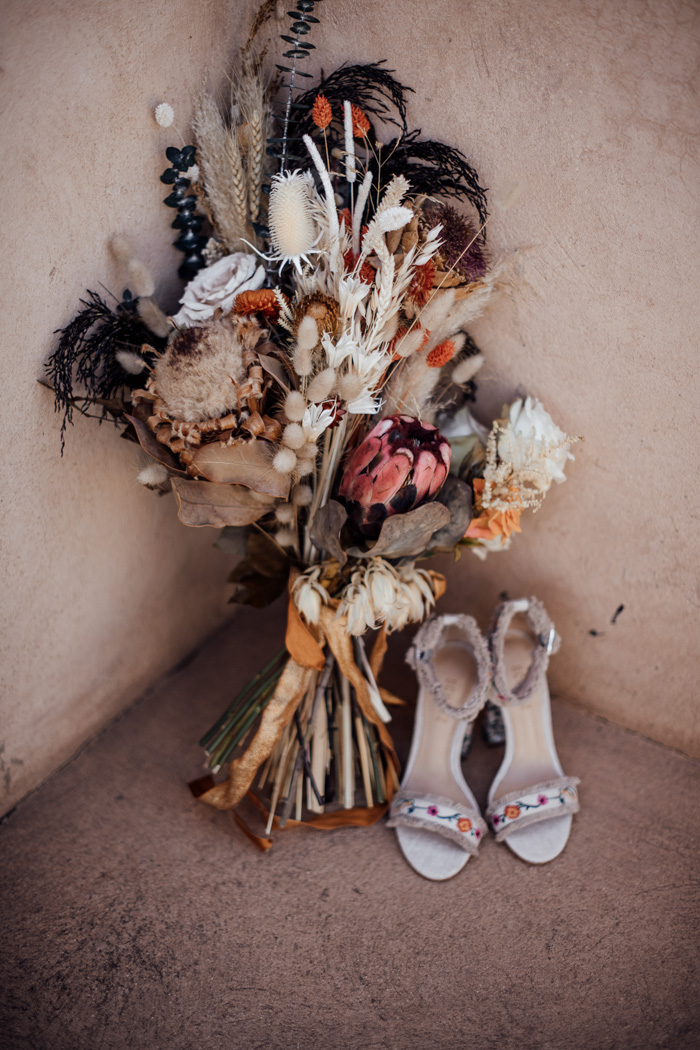 The bride was carrying a chic dried flower bouquet and catchy floral shoes