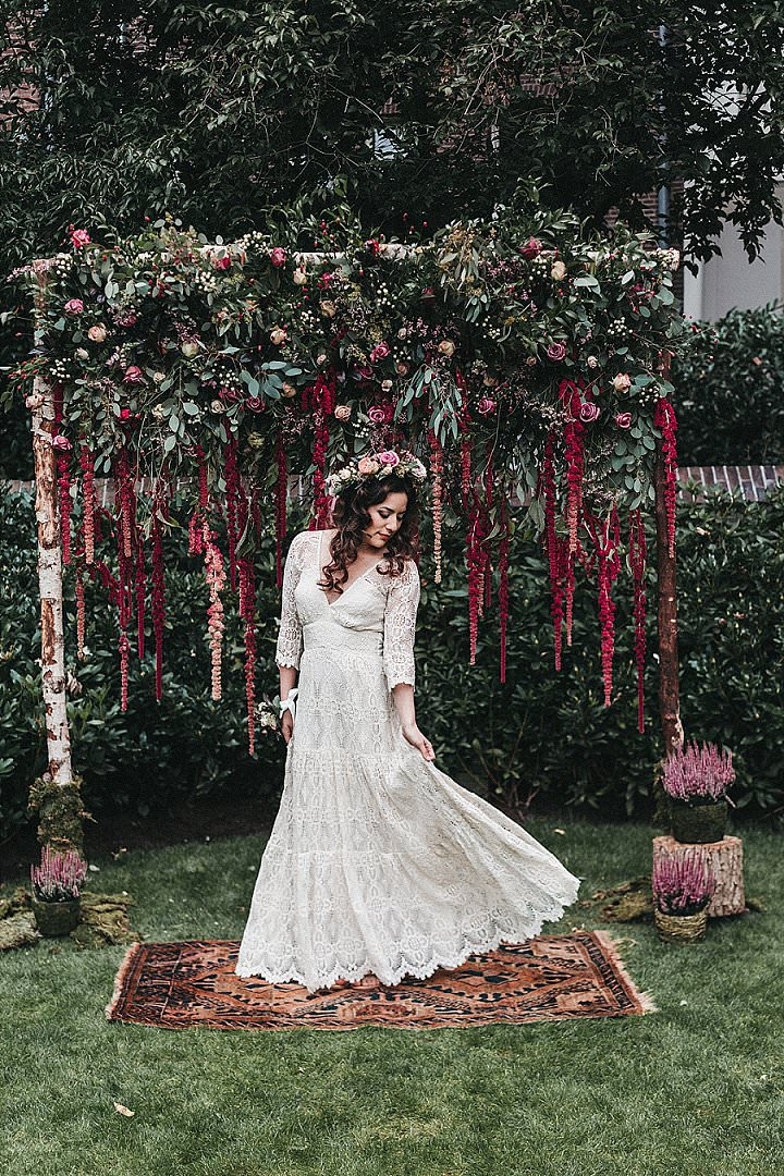 The bride was wearing a boho lace maxi dress with long sleeves and a V-neckline, a fresh floral crown