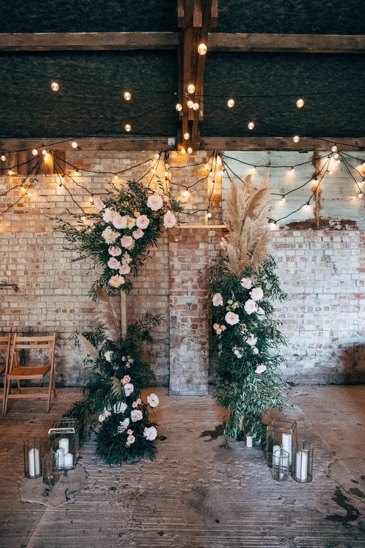 The wedding ceremony space was done with lots of lights, candle lanterns and an arch with lush greenery and blush blooms