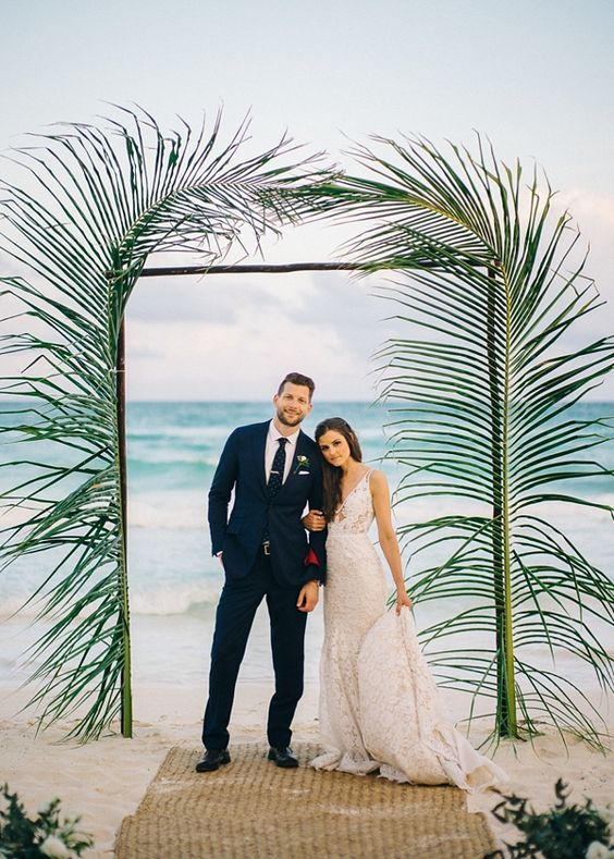 a bamboo wedding arch decorated with giant tropical leaves is a great idea for a beach wedding