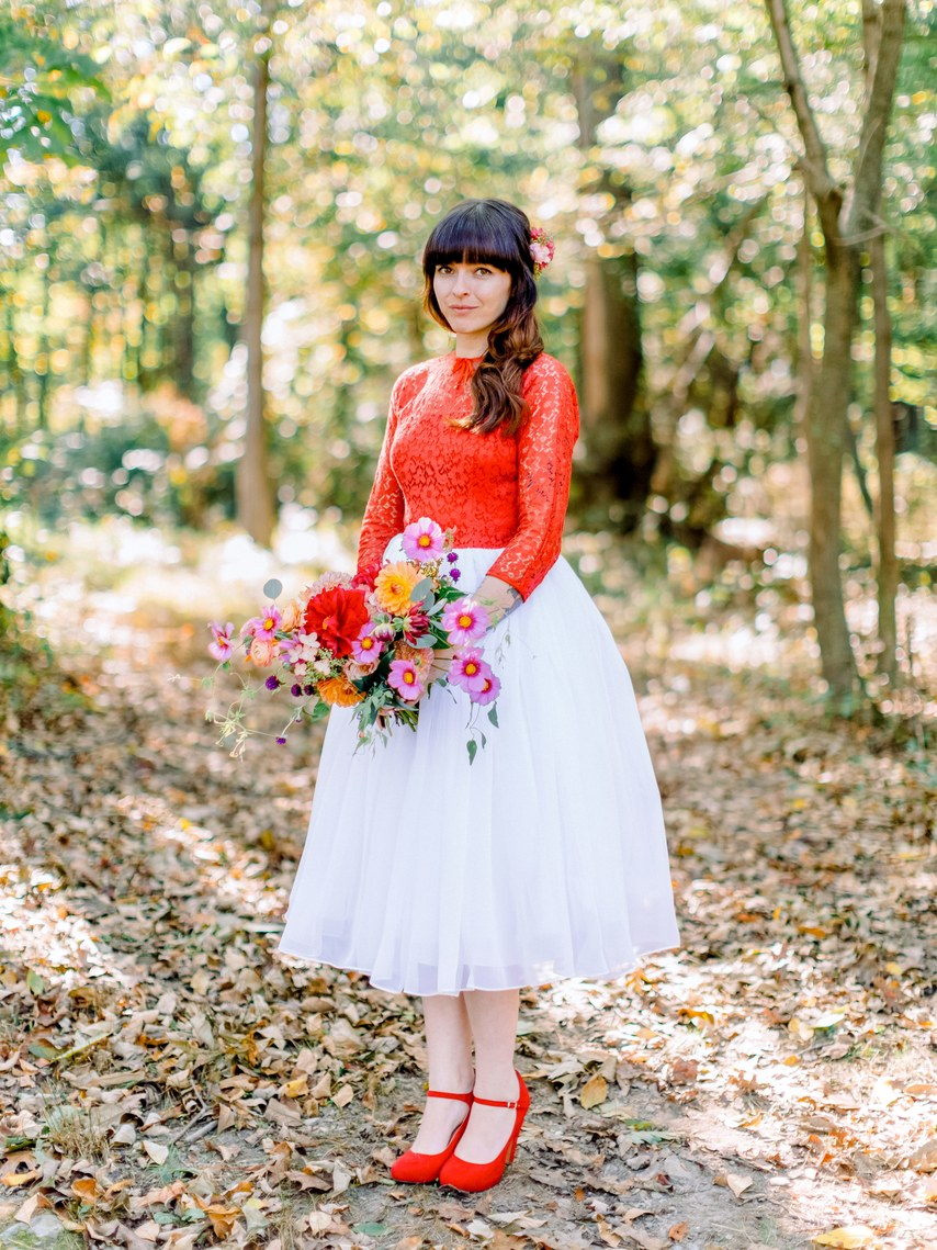 a bright bridal look with a red lace top with long sleeves and matching  shoes plus a tulle white skirt