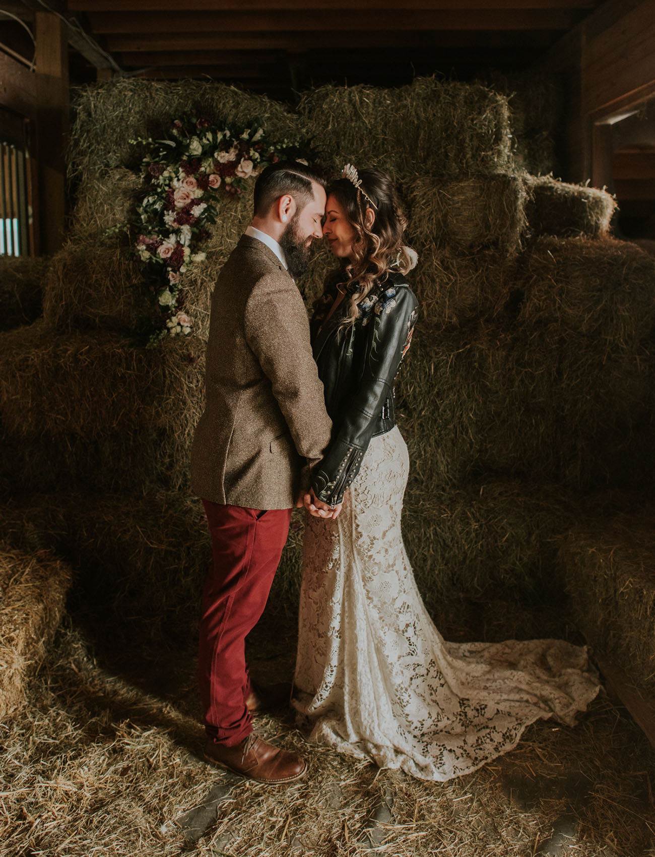 Flower embellished hay bales for a wedding backdrop is a very creative rustic idea