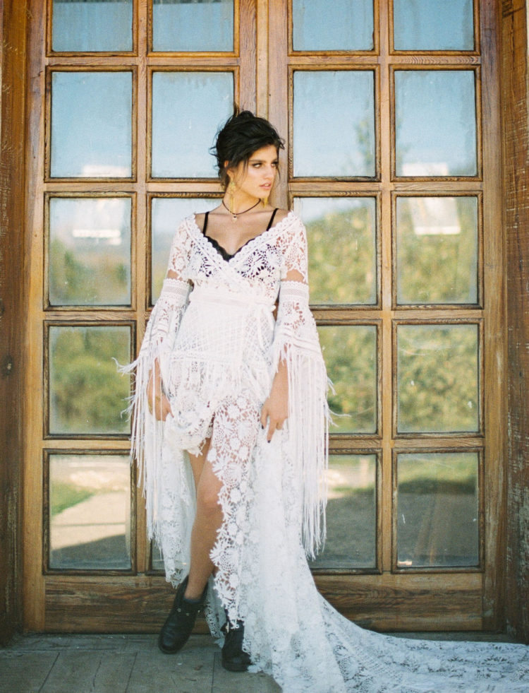 The bride was wearing a boho lace high low wedding dress with a train and black booties