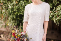 03 The bride was wearing a fully embellished wedding dress with long sleeves, a high neckline and pearl earrings