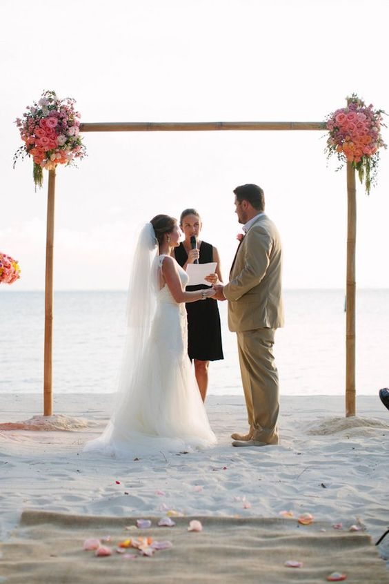 a bamboo wedding arch decorated with lush pink and orange blooms and some greenery