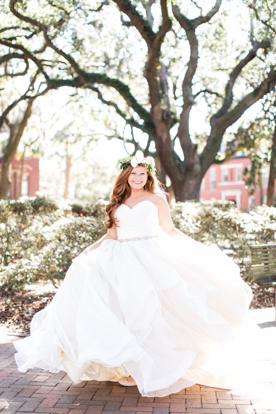 a cute strapless wedding ballgown with a sweetheart neckline, an embellished sash and a layered skirt