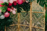 03 a simple tropical backdrop of a wicker screen, monstera leaves, bright balloons and tropical flowers