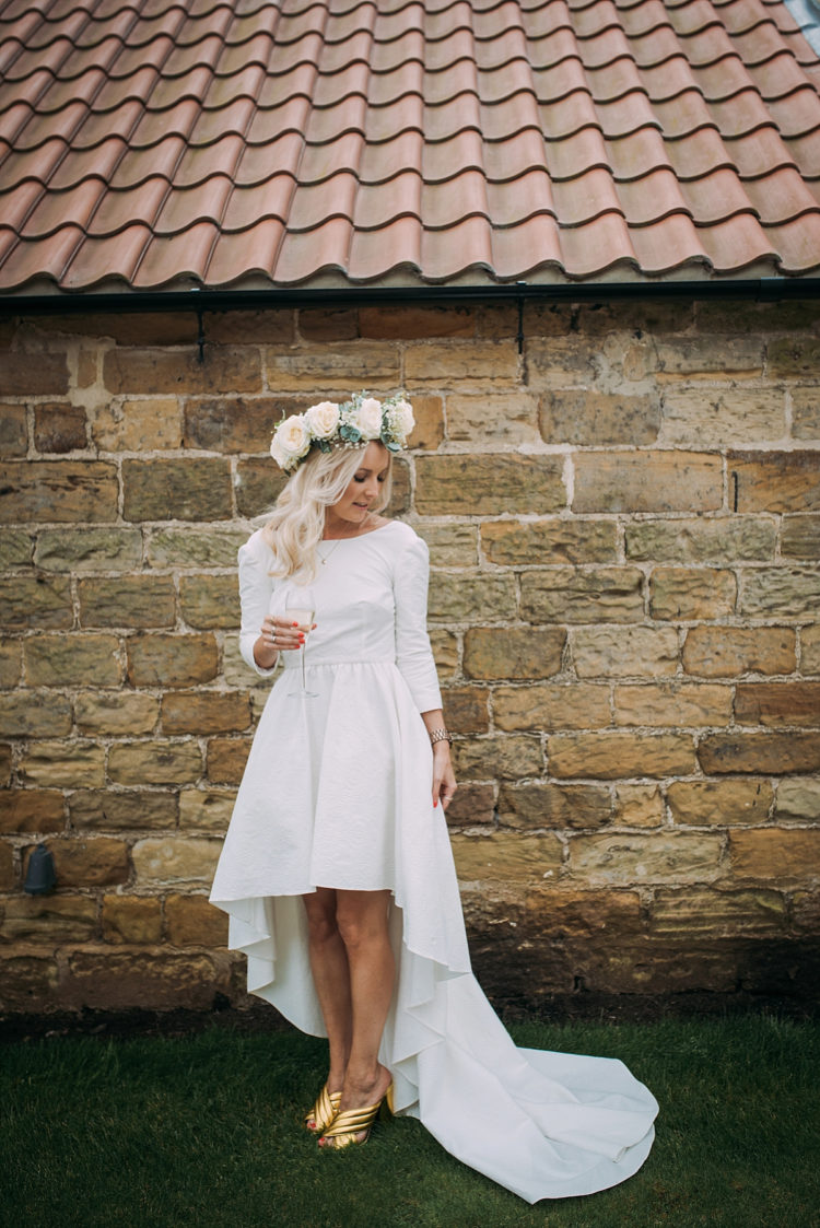 a textural high low wedding dress with long sleeves and a train plus gold mules that add a shiny touch