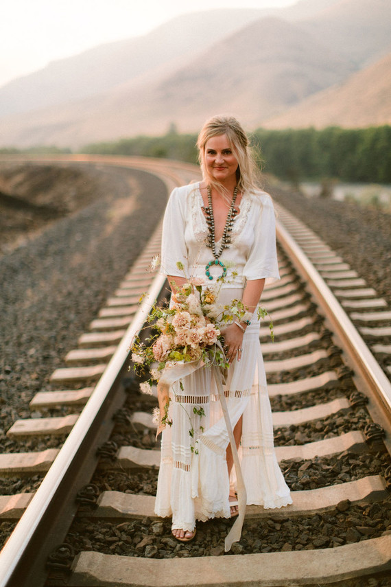 The bride was wearing a boho wedding dress with long sleeves, a V-neckline and a side slit