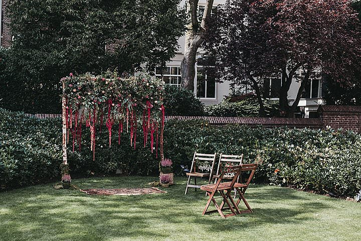 The wedding arch in the garden of Waldorf Astoria was done with crimson blooms and lush greenery