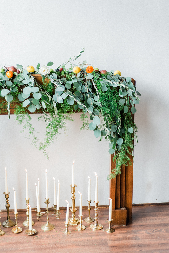 The wedding ceremony space was done with lots of greenery. bold blooms and candles in gold candle holders