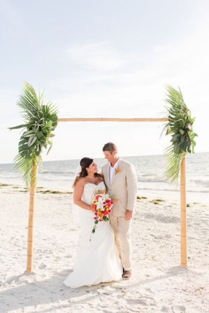 a bamboo wedding arch decorated with lush tropical greenery is amazing for a tropical beach wedding
