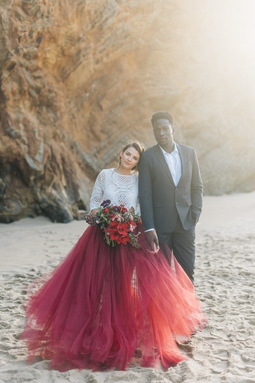 a bold color block bridal outfit with a white boho lace top with long sleeves and a burgundy tulle skirt