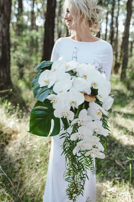 a chic modern cascading wedding bouquet of white orchids, monstera leaves and some greenery