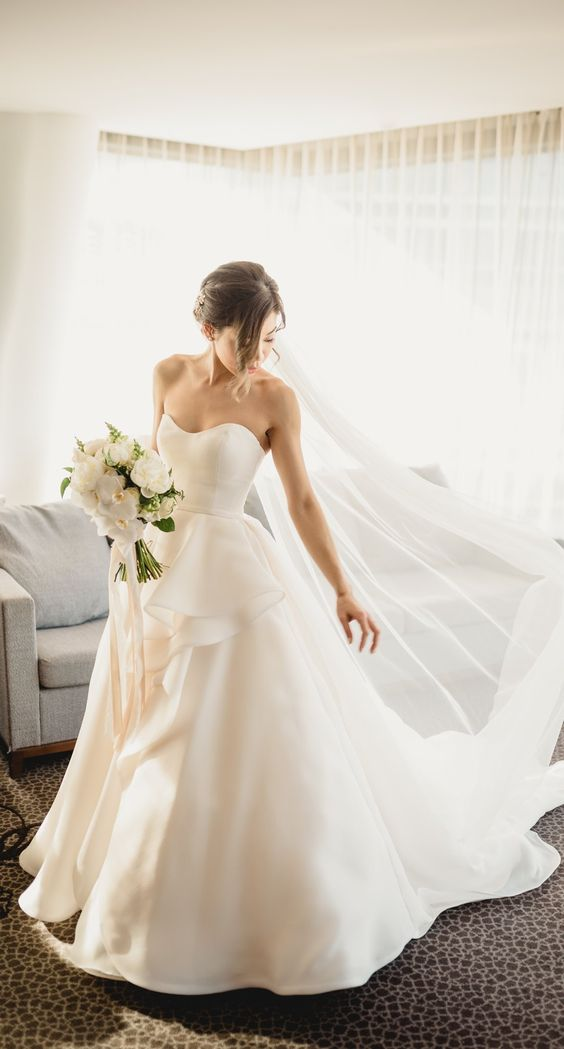 an elegant wedding ballgown with a sweetheart neckline and ruffles on the skirt plus a train
