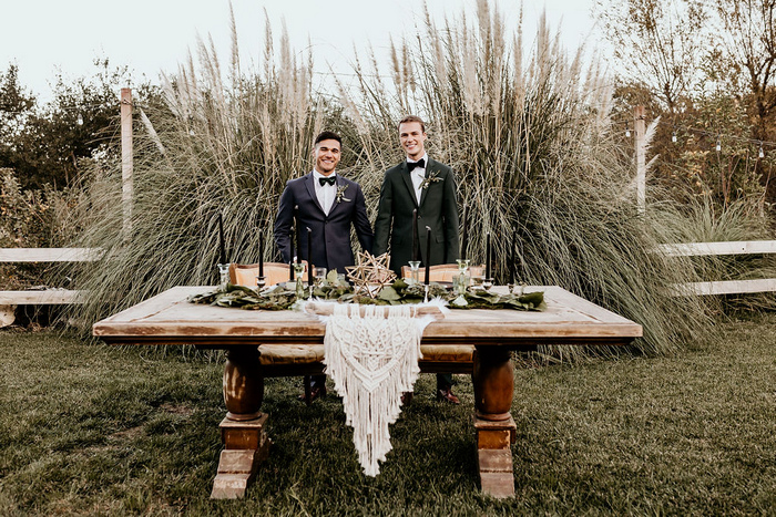 The reception table was styled with macrame, greenery, black candles and a vintage rustic table