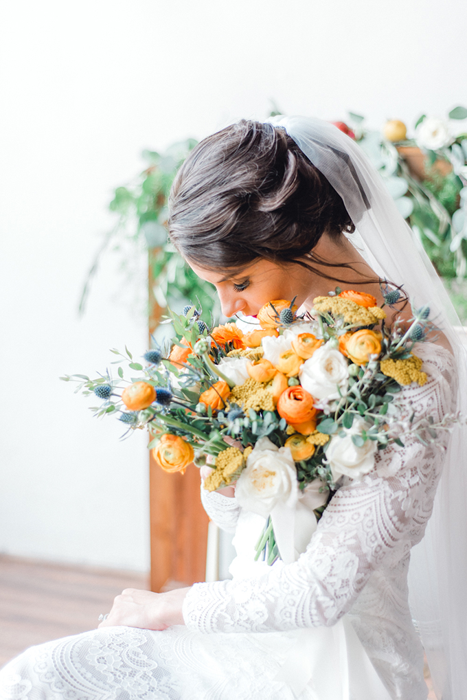 The wedding bouquet was done with yellow and creamy blooms and blue thistles