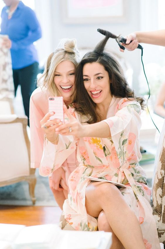 a bride and maid of honor taking some selfies while getting ready in the morning is a fun idea