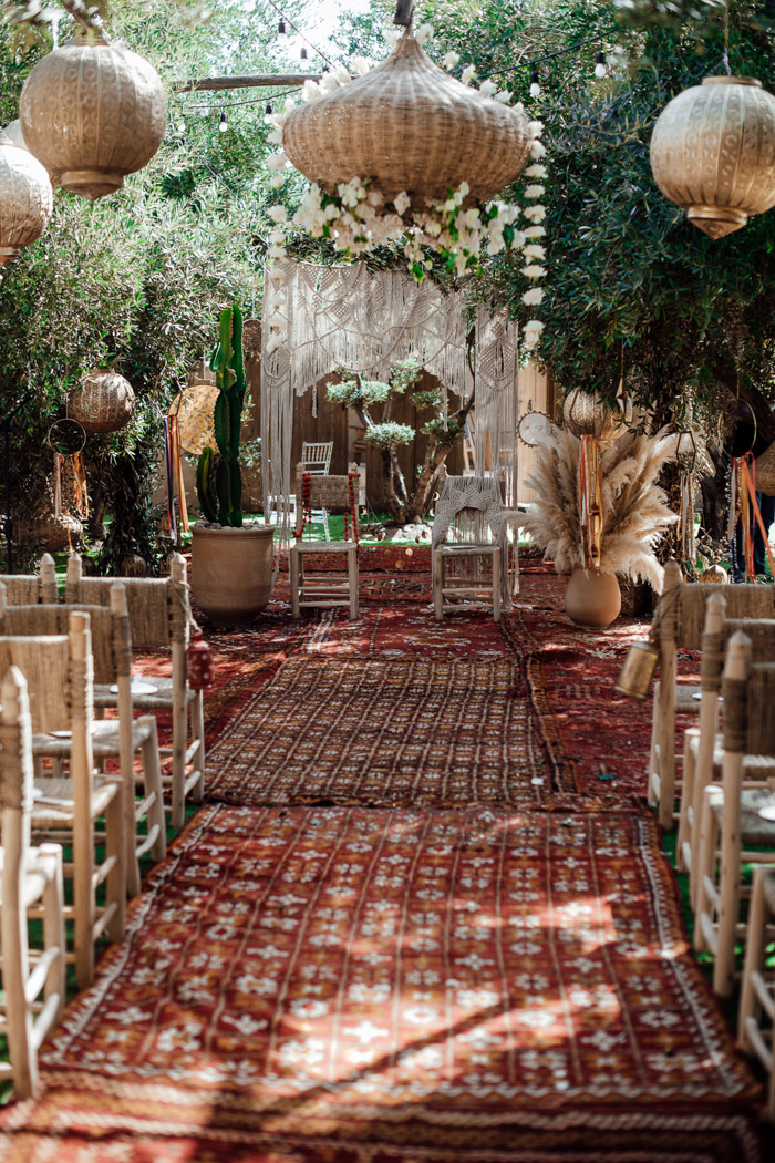 The wedding ceremony space was styled with lots of boho rugs, pampas grass, woven chairs and lamps and tambourines