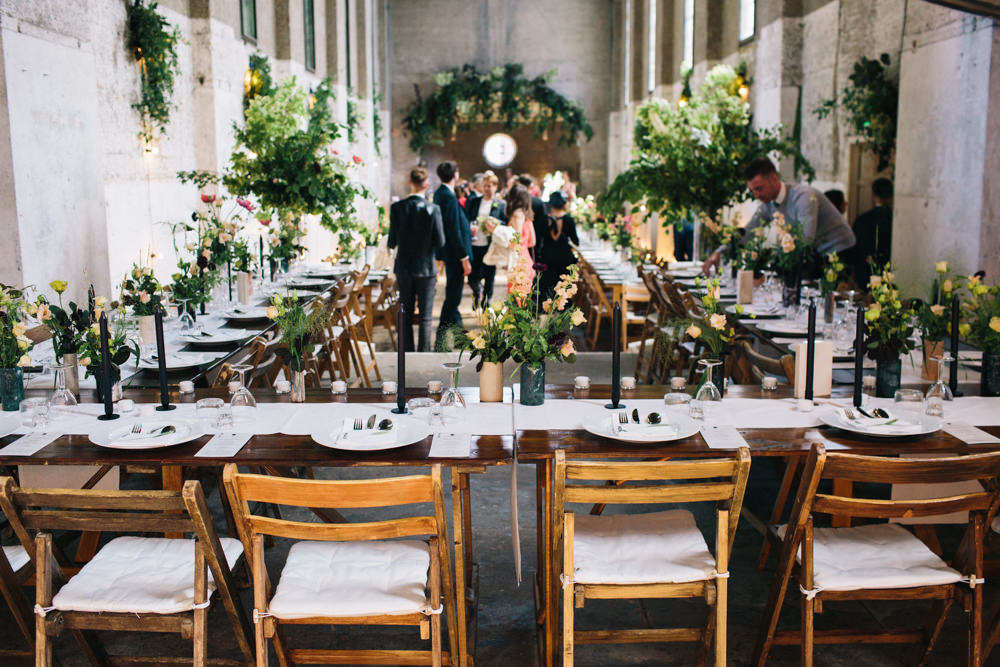 a wedding ceremony space and tables are decorated with lots of greenery