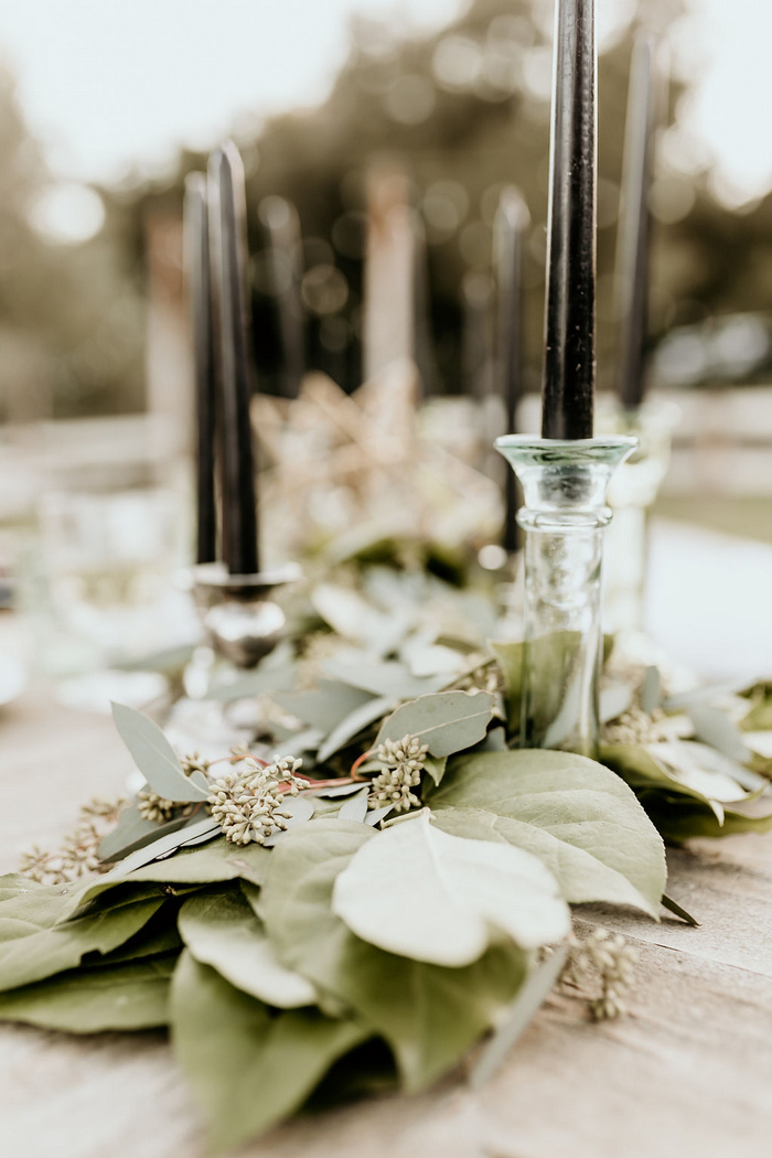 The wedding table runner was made of fresh eucalyptus, with black candles in crystal candle holders