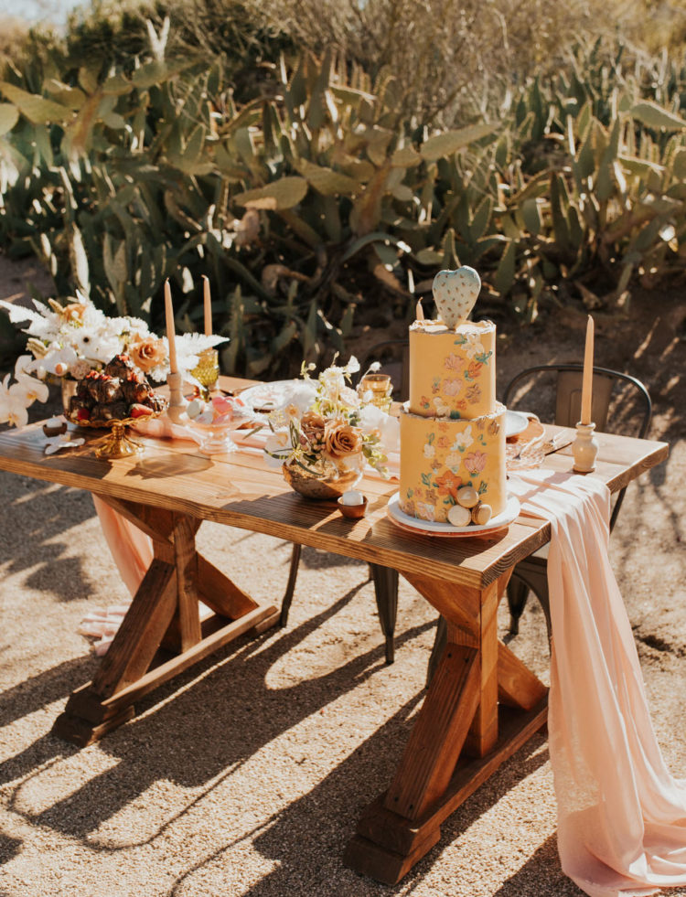 The wedding tablescape was a peachy and blush one, with a long table runner, lush florals and colored glasses