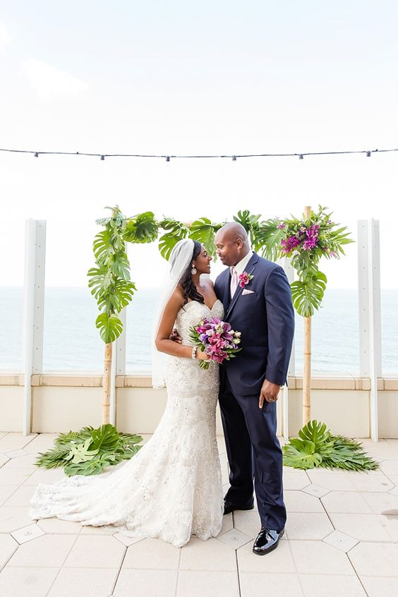 a bamboo wedding arch decorated with tropical leaves and hot pink blooms for a tropical wedding