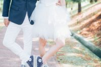06 a chic groom's outfit with a navy blazer, white pants, a blue bow tie and blue denim sneakers and the same sneakers for the bride