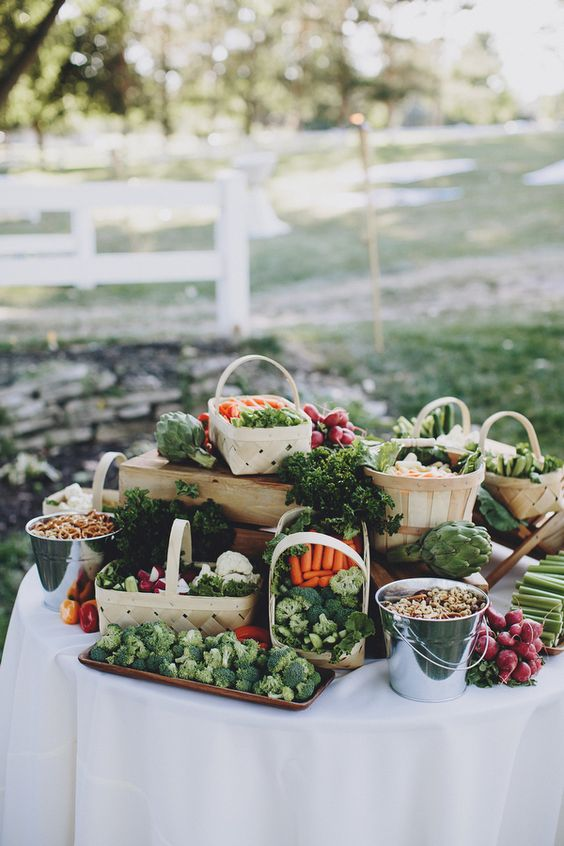 a cute farm-styled fresh vegetable bar done with baskets, trays and buckets