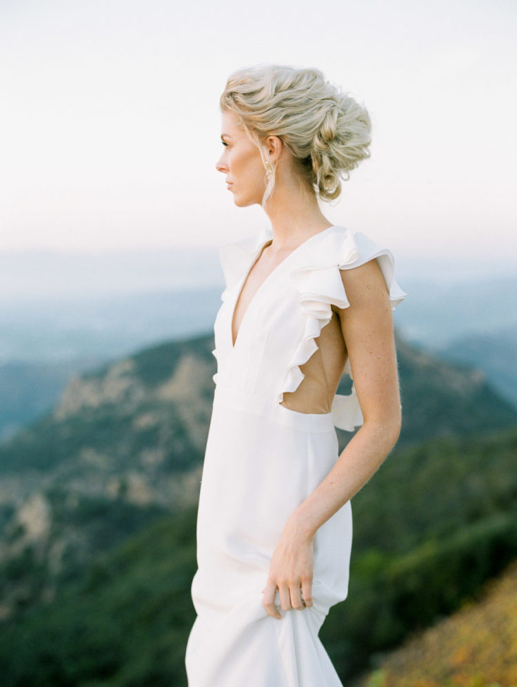 The bride was wearing a plunging neckline with a ruffled bodice and a chic wavy updo