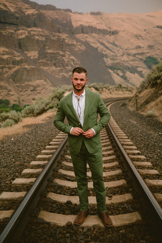 The groom was wearing a green linen suit with a bolo tie