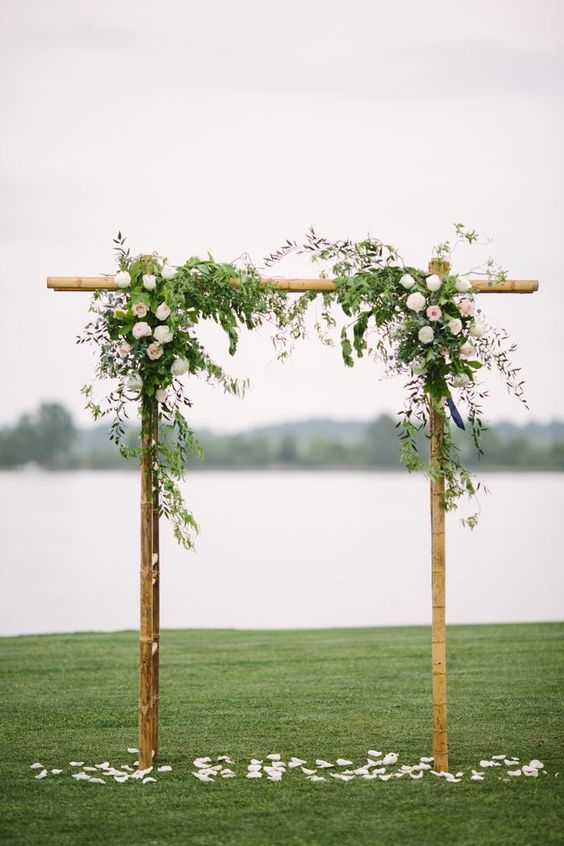 a bamboo wedding arch decorated with textural greenery and roses plus petals on the ground looks simple and romantic