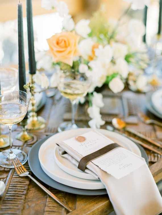 The table setting was done with neutral textiles, matte chargers, black candles and neutral and muted tone blooms